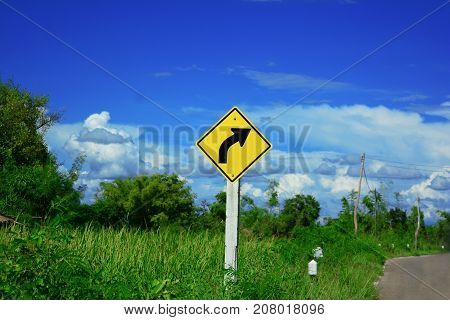 the yellow sign beside the road means to beware the curve ahead