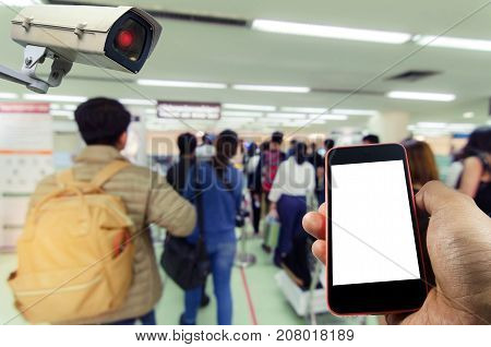 hand holding mobile smart phone and CCTV security camera system operating with blurred image of people at immigration control at airport, internet, surveillance security and safety technology concept