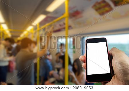 hand holding white blank screen mobile phone with blurred image of people inside subway at train station, people, transportation, internet network connection, technology and social media concept