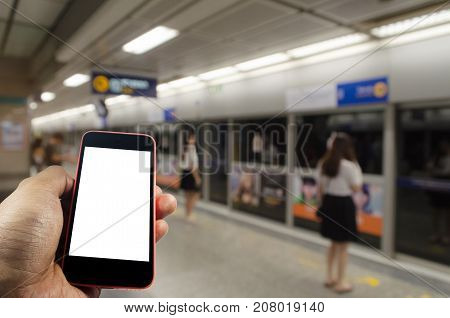 hand holding white blank screen mobile smart phone with people waiting for subway at train station people transportation internet network connection technology and social media concept
