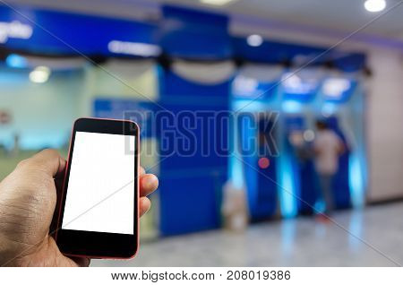 hand holding white blank screen mobile smart phone with blurred image of people queuing to withdraw money from ATM (Automated Teller Machine) internet connection technology and social media concept