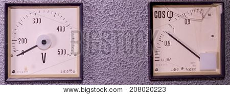 Two old analog instruments - Power factor meter  and voltmeter isolated on grey background