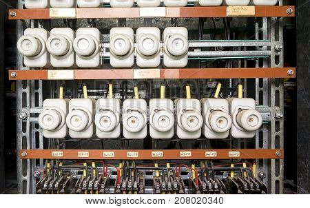 An old fuse box with cables and contactors.  Old electrical panel, electrical box, control panel. Potcelain fuses.