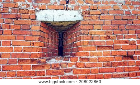 Loophole in the wall. The old years. The spoiled brick is vintage. Brick wall made of red stone background.