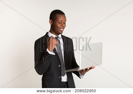 Businessman in stylish suit, tie standing, hand in fist, holding laptop at hands. Portrait. Winner concept, copy space