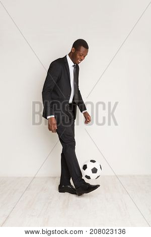 Young african american businessman in suit and tie playing soccer ball