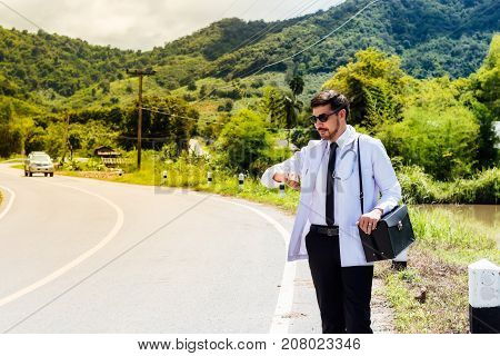 Asia young docter are looking watch at rural road .Community Health and Development Hospital In Remote Areas Development Fund Concept.