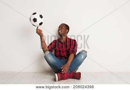 Happy african-american man succeeds in spinning soccer ball on his finger sitting with crossed legs on a white background