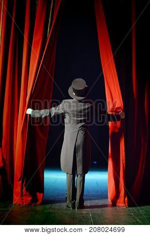 the actor in a tuxedo opens the theater curtain