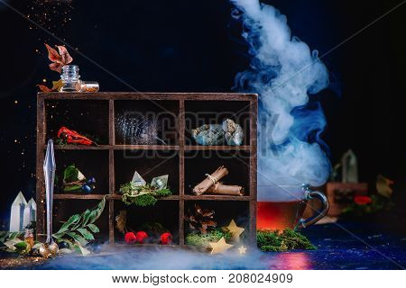 Steaming Cup Of Tea In A Magical Still Life With Potion Ingredients, Berries, Feather, Scrolls, Crys