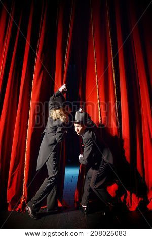 actors in tuxedos open red theatre curtain