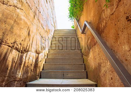 Empty concrete staircase and metal railing with brown clay wall that going up to the top with sunlight background.