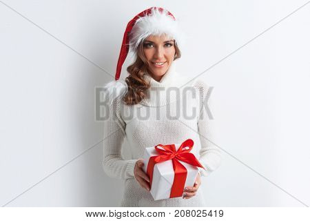 Cute laughing girl in Santa hat holding the gift box