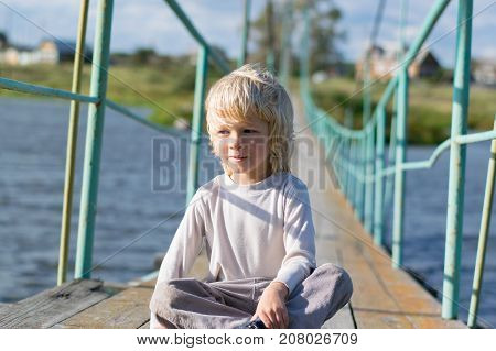 A happy blond boy sitting at an Old wooden pendant bridge - summertime activity at a country village, the Urals, Russiaf, Kuryi