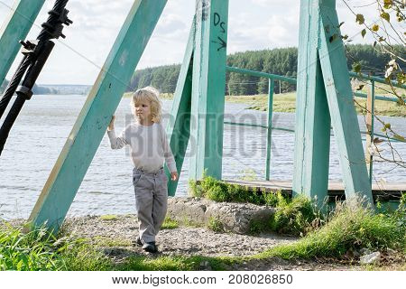 A happy blond boy staying at an Old wooden pendant bridge - summertime activity at a country village, the Urals, Russiaf, Kuryi