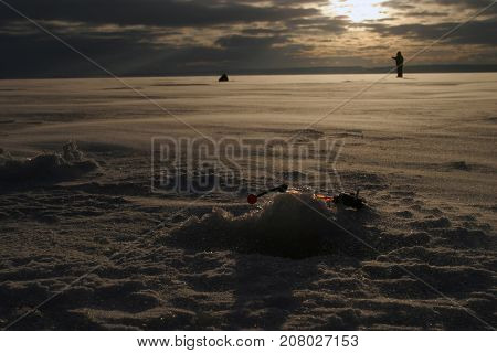 Fisherman On The River Covered With Ice