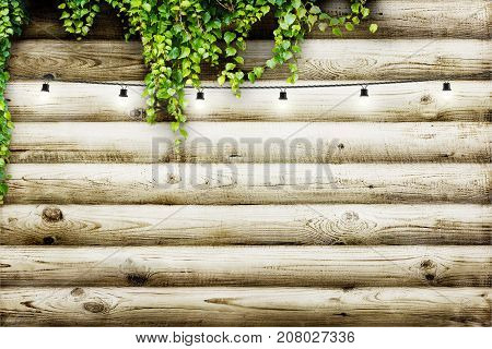 Photo of garland lamps over wooden board fence with green leaves. Decoration background