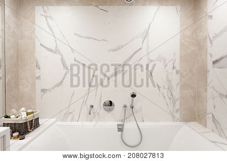 Bathroom interior. Bright bathroom with new tiles. Chrome shower faucet white bathroom