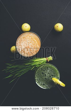 Ayurvedic or medicinal Wheat grass juice with lemon slice and Amla Juice or Avla drink in glass, selective focus