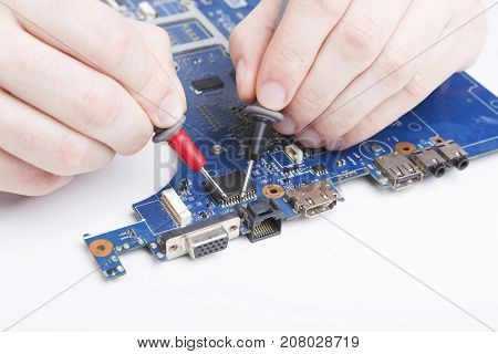 Laptop motherboard testing in service center close-up. Diagnostics of broken computer, electronics repair shop concept, copy space