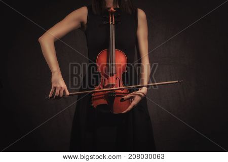 hands of Violinist Woman playing violiln on black background