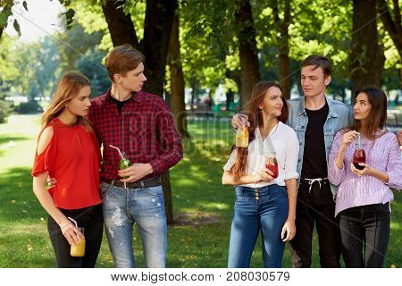 Jealousy and envy in friends relationship. Cheerful young people with detox cocktail having outdoor summer party