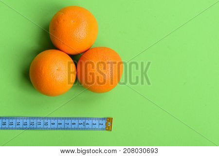 Pattern Made Of Oranges Near Tape Measure In Cyan Color