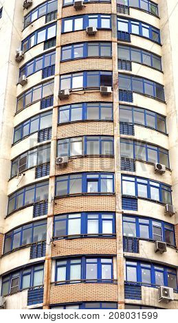 Windows of balconies with air conditioners, brick multi storey house.