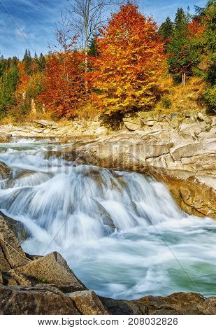Quick mountain stream. Water is washed mountain stones. The river in the autumn forest. The beauty of nature. Travel and Vacation Concept. Hiking