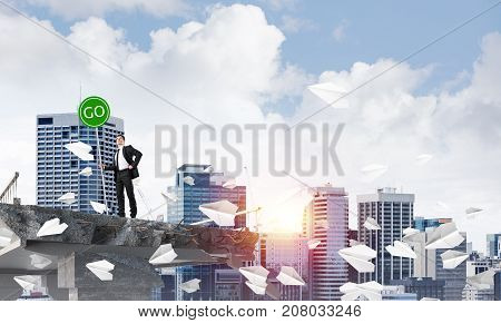 Confident businessman in suit holding green go sign while standing among flying paper planes on broken bridge with cityscape and sunlight on background. 3D rendering.