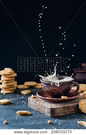 Levitating Milk Splash In A Clay Cup, With Cookies On Dark Rustic Background. Creative Snack Concept
