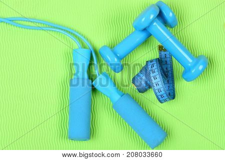 Dumbbells And Jump Rope In Cyan Color On Green Background