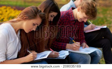 Paperwork, teamwork, social poll , students education, friends lifestyle concept. Group of people fill documents outdoor