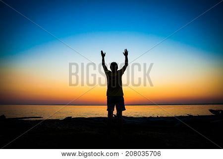 Man Silhouette Praying at the Sunset on the Sea Background