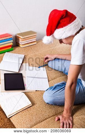Teenager in Santa's Hat doing Homework on the Couch