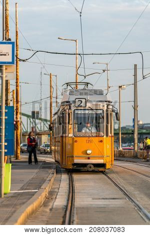 Yellow tram in Budapest and passenger at tram stop. Budapest Hungary - September 25 2017: Close up front view of a yellow tram approaching a tram stop in Budapest Hungary to pick up passengers. Male tram driver looking through window and a female passenge
