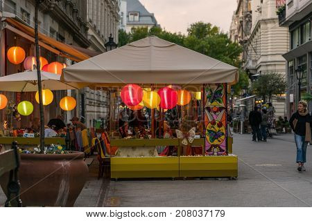 Outdoor street restaurant with people in Budapest. Budapest Hungary - September 25 2017: Street view of people in outdoor restaurant with colored rice lamps eating dinner. Pedestrian street Vaci utca in Budapest Hungary with incidental people walking by.
