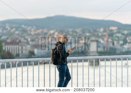 Man walking on bridge looking at his mobile phone. Budapest Hungary - September 25 2017: Close up side view of a pedestrian with glasses and backpack walking by a steel railing on a bridge with the city of Budapest Hungary in the background. Concentrated