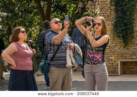 Tourist family taking pictures at public square in Budapest. Budapest Hungary - September 27 2017: Close up front view of two females and one male caucasian tourist at a public square in Budapest Hungary. Walking around to take picures of the surroundings