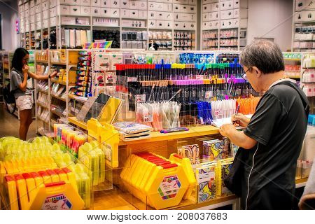 NONTHABURI THAILAND - OCTOBER 08: Unidentified elderly man tries out the color pens in a MINISOLife shop in CentralPlaza Westgate in Nonthaburi on October 08 2017.
