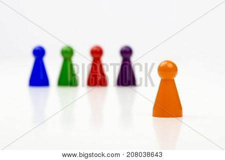 Close-up photo of a group of different-colored pieces in different positions on a white background - applicable to the team view