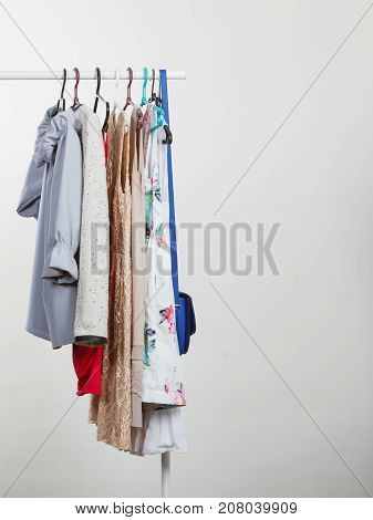 Wardrobe furniture concept. Many clothes on hangers in closet. Studio shot on grey background.