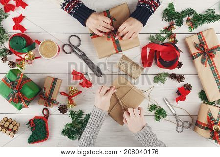 Creative diy hobby. Making modern handmade christmas present, boxes in craft paper, satin ribbon. Top view of two women's hands on messy white wood table with fir tree branches, bells, gift decoration