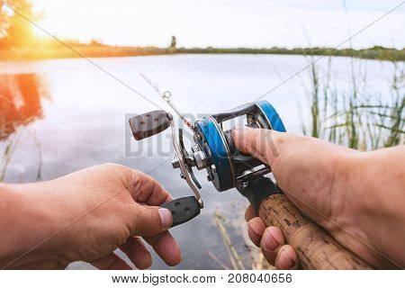 A man is fishing with a backcasting reel. Hands, a rod and a backcasting reel in the background of the rising sun