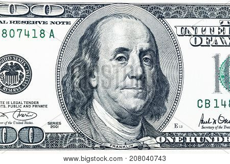 Close up overhead view of Benjamin Franklin face on 100 US dollar bill. US one hundred dollar bill closeup. Heap of one hundred dollar bills on money background.