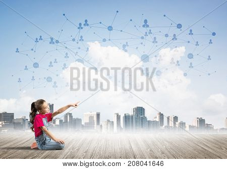 Cute kid girl sitting on wooden floor and pointing with finger