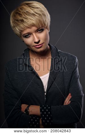 Beautiful Serious Business Woman With Short Bob Blond Hairstyle In Suit On Grey Background. Closeup