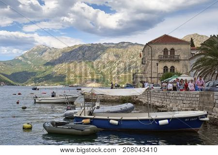 MONTENEGRO, PERAST - AUGUST 13, 2017: Tourists go along the embankment of Perast in the background the Palace of Buyoviches