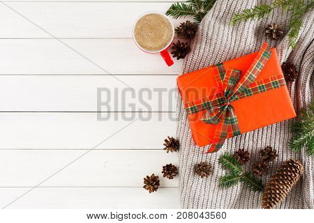 Prepare for xmas. New year decoration. Christmas presents on white wood table background. Handmade scarf, xmas box, fir branch, cup of coffee. Top view, copy space. Winter holiday concept