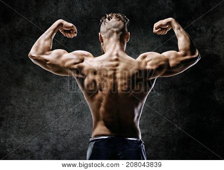 Muscular back of man flexing his arms. Rear view of fitness model with masculine physique on dark background.